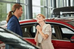 Happy young wife asking to buy a new car for her in the dealership. Caucasian blonde women begging her boyfriend to buy luxury car in the dealership royalty free stock photography