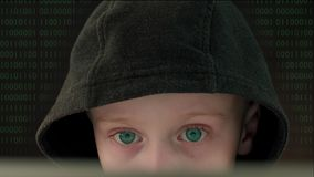 Child hacker in black hoodie. Caucasian boy with blue eyes looks at laptop screen in dark, focused child hacker in black hoodie looking for information on stock footage