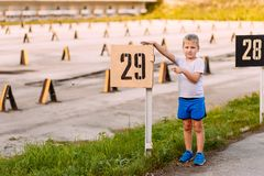 Caucasian boy in blue shorts and sneakers shows the pointer with the number stock images