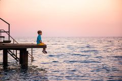 Caucasian boy in a blue striped t-shirt and yellow shorts sits on a pier, having given legs to the sea, and enjoys at sunset royalty free stock photography