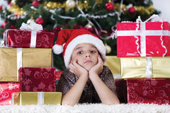 Caucasian boy dreaming about presents at christmas time Stock Image