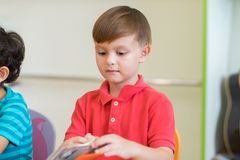 Caucasian boy ethnicity kid learning in classroom with friends a royalty free stock photography