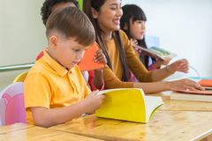 Caucasian boy ethnicity kid reading book white learning in classroom with friends and teacher in kindergarten school, education royalty free stock photos