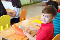 Caucasian boy ethnicity kid smiling in classroom with friends in royalty free stock photos