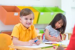 Caucasian boy ethnicity kid smiling white learning in classroom. With friends and teacher in kindergarten school, education concept royalty free stock images
