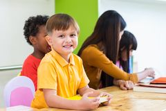 Caucasian boy ethnicity kid smiling white learning in classroom. With friends and teacher in kindergarten school, education concept royalty free stock image