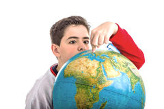 Caucasian boy hidden behind globe points index finger Royalty Free Stock Image