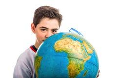 Caucasian boy hidden behind globe points index finger stock image