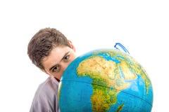 Caucasian boy hidden behind globe Stock Photo