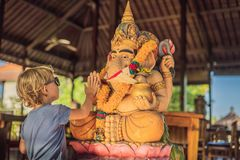 Caucasian boy high-five Ganesha. Meeting Western and Eastern culture concept. oriental and occidental. Traveling to Asia with chi. Ldren royalty free stock photos