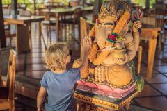Caucasian boy high-five Ganesha. Meeting Western and Eastern culture concept. oriental and occidental. Traveling to Asia with chi. Ldren royalty free stock photography