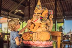 Caucasian boy high-five Ganesha. Meeting Western and Eastern culture concept. oriental and occidental. Traveling to Asia. With children stock images