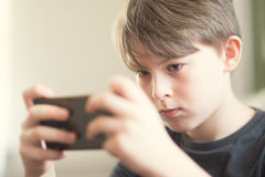 Caucasian boy at home. A boy sending a text message or playing a game on smartphone Stock Images