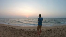 Young man makes a photo during sunset. Caucasian boy is making photo at the Srilankian sea stock footage