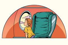 Caucasian boy passenger looks out the window on an airliner Royalty Free Stock Photos
