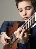 Caucasian  boy playing on acoustic guitar. Stock Photos