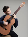 Caucasian  boy playing on acoustic guitar. Royalty Free Stock Photos