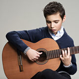 Caucasian  boy playing on acoustic guitar. Royalty Free Stock Images