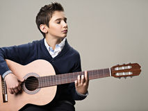 Caucasian  boy playing on acoustic guitar. Stock Images