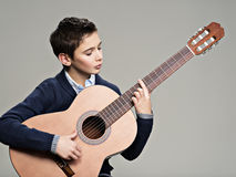 Caucasian  boy playing on acoustic guitar. Stock Photography