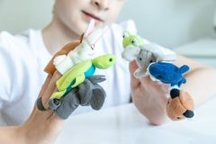 A caucasian boy playing different roles by using finger puppets, toys for expressing his emotions, agression, fear and freandship stock image