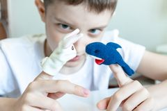 A caucasian boy playing different roles by using finger puppets, toys for expressing his emotions, agression, fear and freandship royalty free stock photo