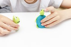 A caucasian boy playing different roles by using finger puppets, toys for expressing his emotions, agression, fear and freandship. As a part of psychotherapy stock photography