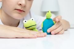 A caucasian boy playing different roles by using finger puppets, toys for expressing his emotions, agression, fear and freandship stock photos
