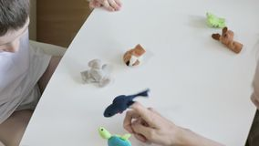A caucasian boy playing with psychologist, psychotherapist different roles by using finger puppets, toys for expressing. His emotions, agression, fear and stock video