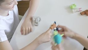 A caucasian boy playing with psychologist, psychotherapist different roles by using finger puppets, toys for expressing. His emotions, agression, fear and stock video footage
