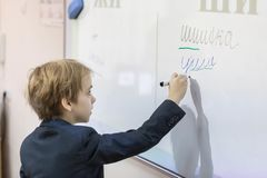 Caucasian boy at school at a board. The boy writes on a board of a word royalty free stock photos