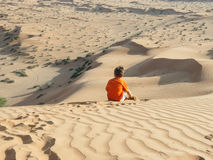 Caucasian boy sitting on sand dune rear view Royalty Free Stock Photography