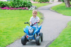 Caucasian boy toddler driving blue electric car on the road Stock Images