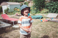 Caucasian boy wearing stripped tshirt and hat with funny face expression outside on house backyard on summer day, crying. Portrait of cute Caucasian boy wearing royalty free stock photos