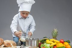 Caucasian Boy Working With Whisk In Cooking Hat. Royalty Free Stock Image