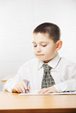 Caucasian boy writing at the desk Royalty Free Stock Photo