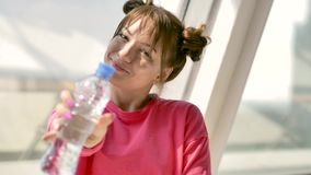 Caucasian brunett i rosa sportsweardricksvatten från flaskan i vitt rum arkivfilmer