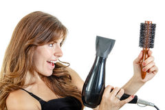 Caucasian brunette female hairdresser holding hairdryer and bruc Stock Image