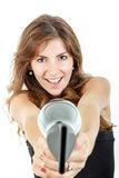Caucasian brunette female hairdresser holding hairdryer like gun Royalty Free Stock Photography