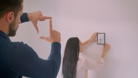 Caucasian brunette girl choosing place for framed picture on white wall while her boyfriend makes frame shape with. Fingers stock video footage