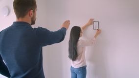 Caucasian brunette girl hanging framed picture on white wall while her boyfriend commands the right place for it. Caucasian brunette girl hanging framed picture stock video