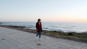 Caucasian brunette girl in sunglasses, red shirt and jeans walking along beach. Young charming woman in red swimsuit and blue jean. S walks along beach promenade stock footage