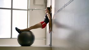 Caucasian brunette in sportswear does exercises with a gymnastic ball. In the white hall, in the background is a stained glass window and a machine for a stock footage