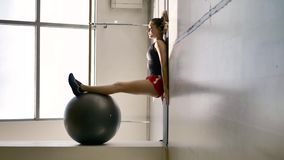 Caucasian brunette in sportswear does exercises with a gymnastic ball. In the white hall, in the background is a stained glass window and a machine for a stock video