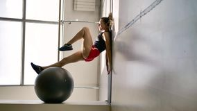 Caucasian brunette in sportswear does exercises with a gymnastic ball. In the white hall, in the background is a stained glass window and a machine for a stock video footage