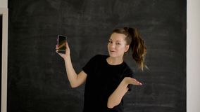 Caucasian brunette in sportswear holds a smartphone in her hand and shows class stock video