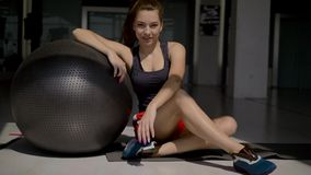 Caucasian brunette in sportswear sitting on the floor,leaning on gymnastic ball. Caucasian brunette in sportswear sitting on the floor, leaning on a gymnastic stock video footage