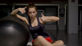 Caucasian brunette in sportswear sitting on the floor,leaning on gymnastic ball. Caucasian brunette in sportswear sitting on the floor, leaning on a gymnastic stock video