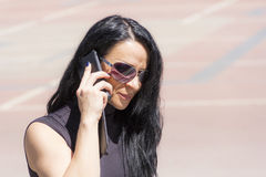 Caucasian brunette in sunglass talking by mobile Royalty Free Stock Image