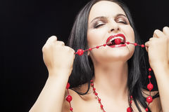 Caucasian Brunette Woman Biting Her Long red Beads Stock Photography